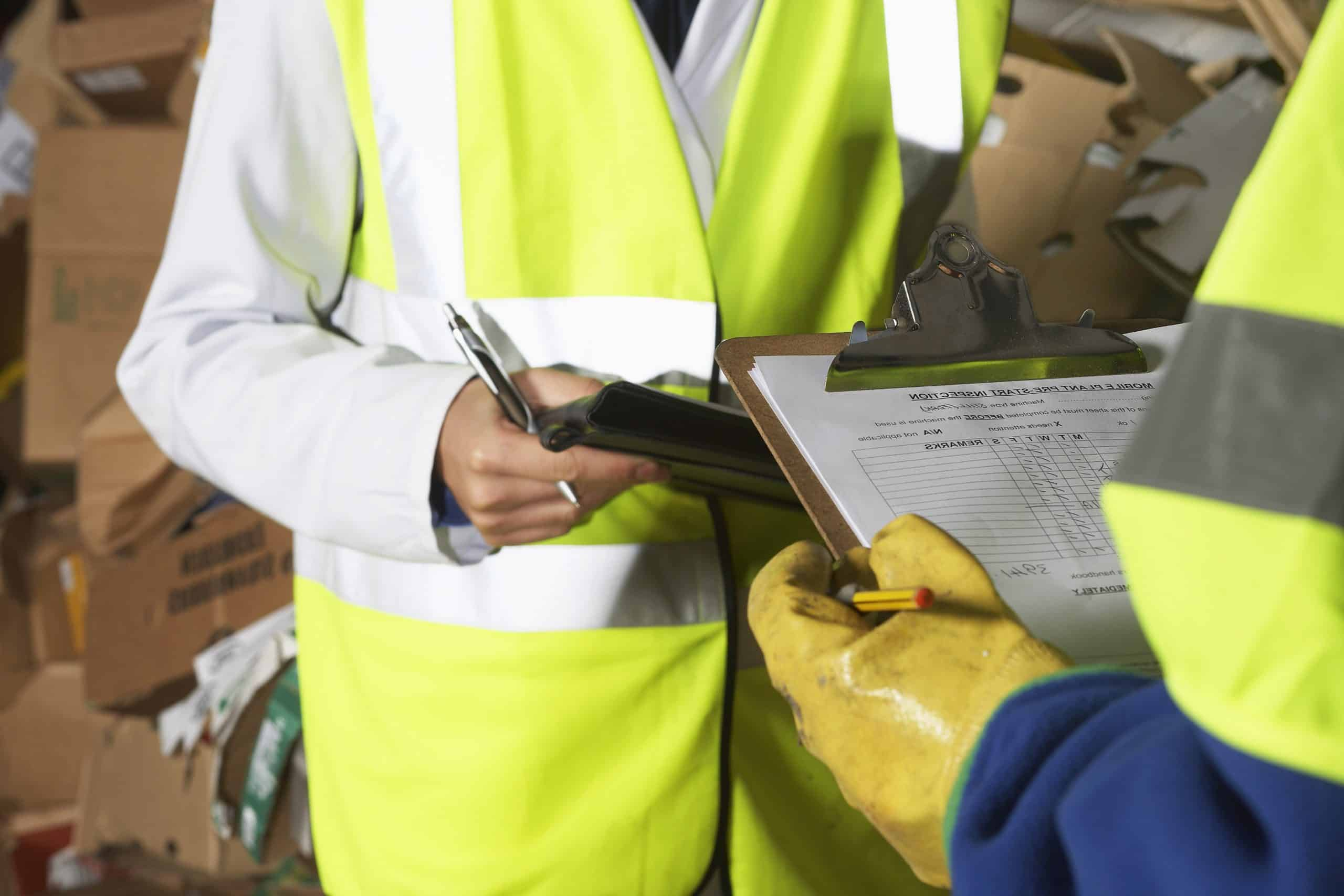 Midsection of two workers holding clipboards in industry